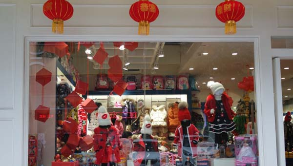 在儿童服装橱窗里面红色的背景,展示着红色的衣服,帽子,围巾,礼物盒子